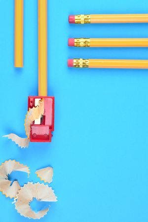 Back to School Concept: Yellow Pencils with a sharpener and shavings, on a blue background. Three pencils with eraser end entering the frame from the top right side with copy space below. Imagens