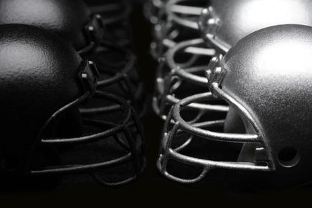 Black and Silver American Football helmets lined up facing each other on a black background. Competition Concept.