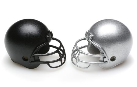 Black and Silver Football Helmets facing each other. Competiton Concept.