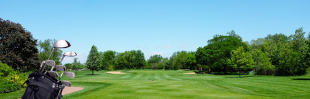 Banner de golf: una bolsa de golf con palos en un tee de par tres. Cielo azul y espacio para copia.