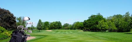 Golfbanner: een golftas met clubs op een par drie tee-box. Blauwe lucht en ruimte voor kopiëren.