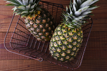 Two Pineapples in a metal shopping basket on a rustic wood surface. Stock fotó