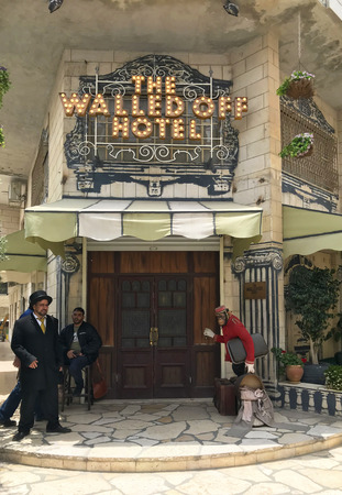 BETHLEHEM, PALESTINE - MAY 12, 2018: Walled Off Hotel front entrance and door men.  The Hotel is an entirely independent leisure facility set up and financed by Banksy. 版權商用圖片 - 110654079