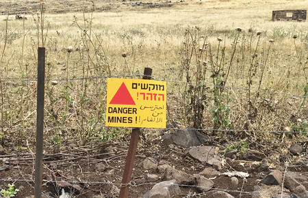 GOLAN HEIGHTS, ISRAEL - MAY 14, 2018: Sign warning of land mines on barbed wire fence near the border of Syria. Wording is translated into multiple languages. Editorial
