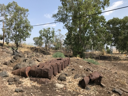 GOLAN HEIGHTS, ISRAEL - JUNE 17, 2018: Oil drums in a field in the Golan Heights of Israel. The rusted drums are remnants of war. Редакционное