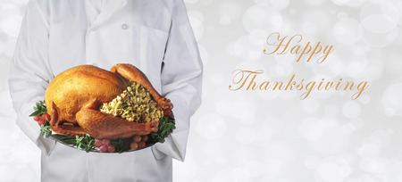 Chef holding a Thanksgiving turkey on a platter over a  silver bokeh background, with Happy Thanksgiving and copy space.
