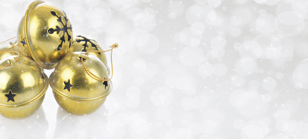 Christmas Concept: Gold Jingle bells on a snowy bokeh silver background with copy space. Stock Photo