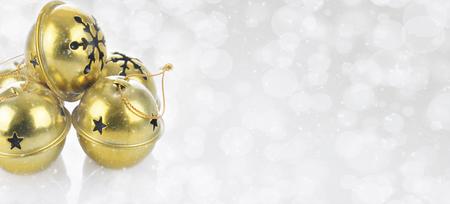 Concetto di Natale: campanelli d'oro su uno sfondo d'argento bokeh innevato con spazio per le copie.