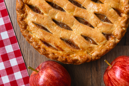 Flat Lay view of a fresh baked apple pie with apples on a rustic wood table. Archivio Fotografico