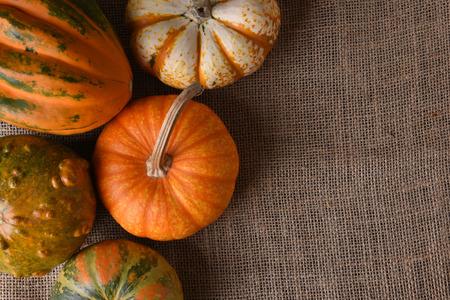 Decorative gourds and pumpkins on a burlap surface with copy space. Banco de Imagens