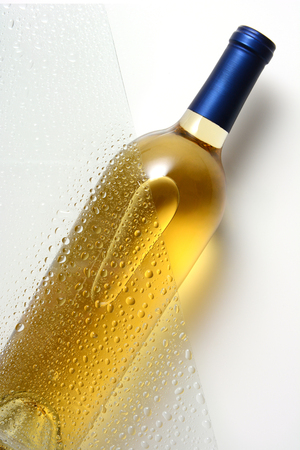 A white wine bottle partially behind a sheet of glass with water drops. Zdjęcie Seryjne