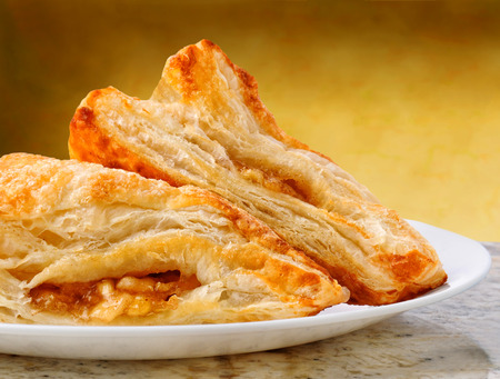 Closeup of two apple turnovers on a plate and granite counter top with warm mottled background.