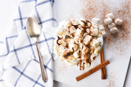 Overhead view of a mug of hot chocolate with toasted marshmallows sprinkled with cinnamon. A spoon towel and cinnamon sticks