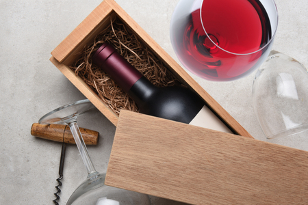 Red Wine Box: A single bottle of Cabernet in a wood box partially covered by its lid with empty glasses and corkscrew with a full glass of red wine .