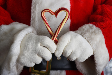Closeup of Santa Claus hands holding two old fashioned candy canes forming a heart shape in front of his torso. Stock Photo