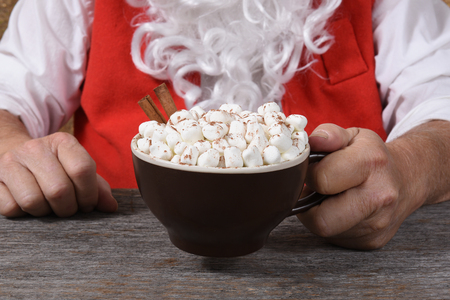 Closeup of Santa Claus holding a mug of hot fresh hot cocoa with marshmallows in his hands. Stock Photo