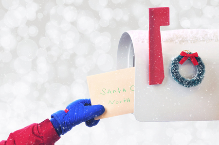 Closeup of a childs hand placing a Letter to Santa in a mail box on a snowy silver bokeh background, with room for your copy.
