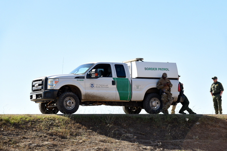 SAN YSIDRO, CALIFORNIA - NOVEMBER 26, 2018: Border Patrol Agents and Vehicle taking a break on the border between the USA and MExico. Editorial