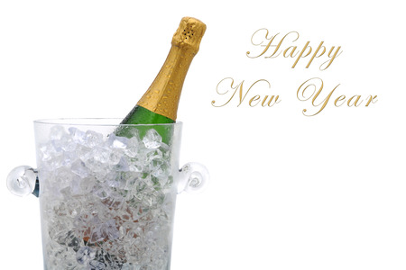 A champagne bottle in a cyrstal ice bucket with the words Happy New Year with room for additional copy.
