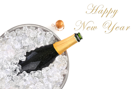 Top view of a champagne bottle in metal ice bucket with the words Happy New Year with room for your copy. Standard-Bild