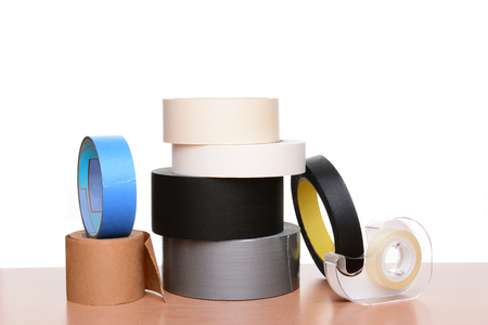 Seven different types of tape on a wood table and white background. Stock Photo