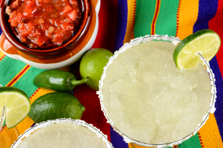 Cinco de Mayo Concept: Margaritas and Salsa on a colorful  table cloth, with limes, and peppers. Zdjęcie Seryjne - 114868662
