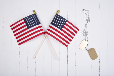 Military Dog Tags and American Flags on white wood background.