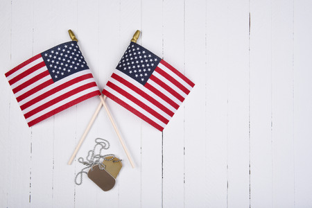 Military Dog Tags and American Flags on white wood background with copy space.