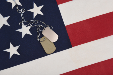 Closeup of military dog tags on the blue star field of an American Flag,