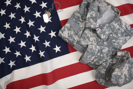 Overhead view of an American Flag with military combat uniform and dog tags. Stock Photo