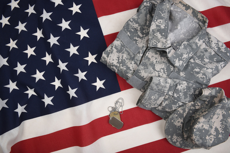 Overhead view of military combat uniform with dog tags on an American Flag. Stock Photo
