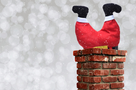 Santa Claus stuck upside down in a chimney over a silver bokeh background with snow effect. Stockfoto