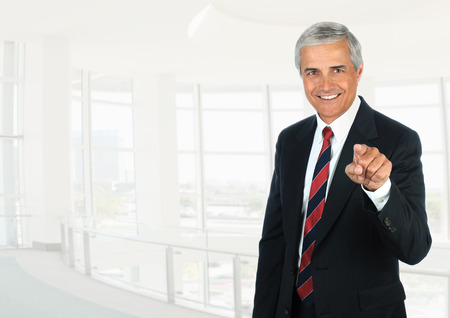 Mature businessman standing in a high key office setting pointing at the camera. Stock fotó