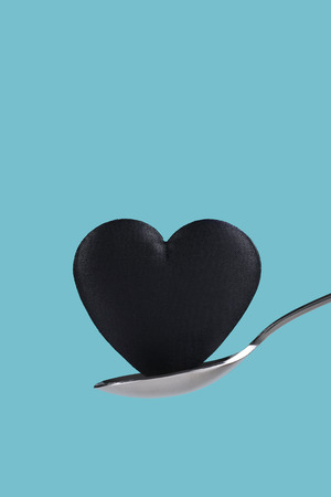 A black heart balanced on a spoon over a teal background. 스톡 콘텐츠