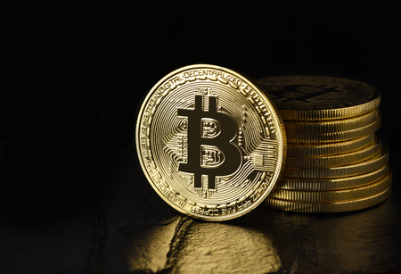 Bitcoin: Physical bit coin aslo called Digital Currency or Cryptocurrency, on edge standing in front of a stack, on black with reflection and copy space.