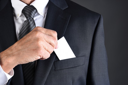 Closeup of a businessman putting a blank business card into his jackets breast pocket. Man is unrecognizable. Banque d'images - 114884498