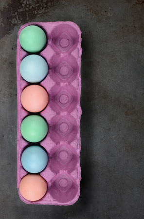 Easter Eggs: A carton of six dyed eggs with room for six more on a metal baking sheet surface.