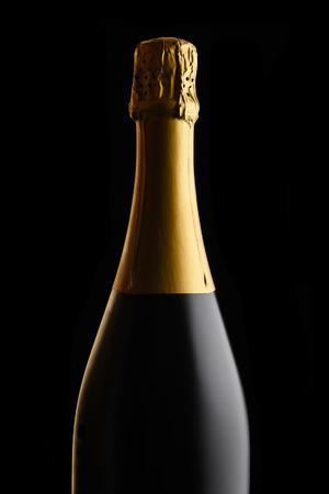 Closeup of an unopened bottle of Champagne against a black background.  Stockfoto