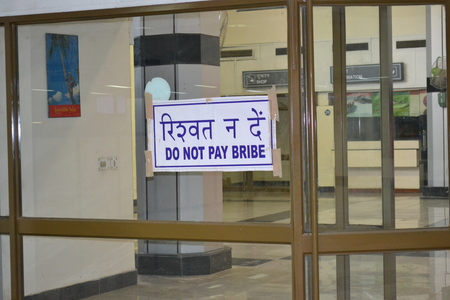MUMBAI, INDIA - OCT 13, 2015: Do not Pay Bribe sign at the Mumbai airport, warning visitors to be wary of scams.