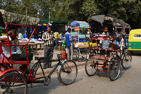 NEW DELHI, INDIA - OCTOBER 28, 2015: Street scene with pedicabs and street vendors.