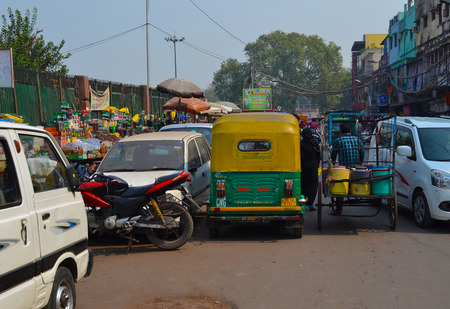 NEW DELHI, INDIA - OCTOBER 28, 2015: Crowded traffic street scene with cars motorcycles and pedicabs.