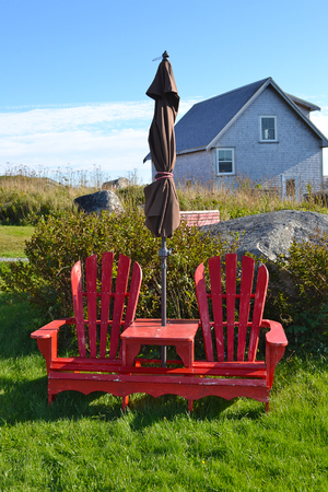 PEGGYS COVE, NOVA SCOTIA - OCTOBER 10, 2011: Red Chairs and table near The Old Red Schoolhouse, built in 1834 Editorial