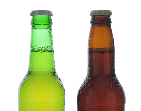 Beer Bottles: Closeup of one green and one brown beer bottle covered with condensation, on a white background. Banco de Imagens