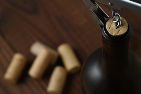 Closeup of a the top of a red wine bottle with the cork being pulled out, horizontal format with copy space.