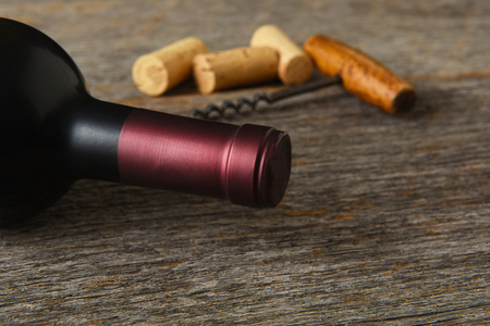 White Wine Still Life: Closeup of a bottle of Cabernet Sauvignon wine with corkscrew and corks on a rustic wood table.