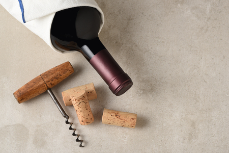 Cabernet Sauvignon Bottle Still Life: A bottle of red wine wrapped in a towel on a gray tile surface the antique cork screw and corks.