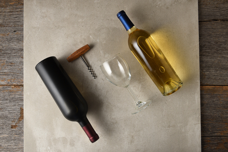 Two bottles of wine on a gray tile surface on a rustic wood table, white wine and red wine. A corkscrew and wineglass are between the bottles.
