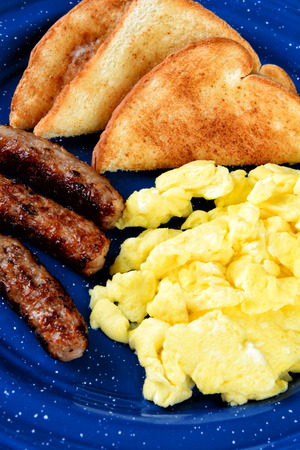 Closeup of a scrambled eggs breakfast with toast and three sausage links on a blue enamelware plate.
