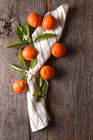 Minneola Tangelos: Closeup of a group of fruit and a towel and leaves on a rustic wood table. Stock Photo