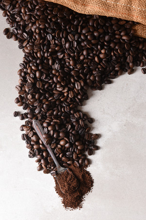 High angle view of a burlap bag of roasted coffee beans spilling onto the surface with a spoonful of coffee grounds at the end of the spill.